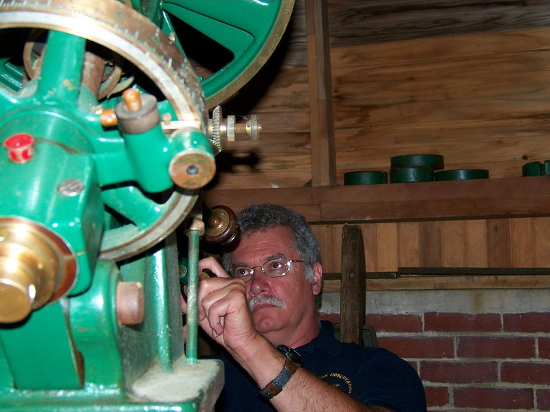 Al Paslow examines workmanship in the Warner & Swasey equatorial mount of the Brashear telescope.