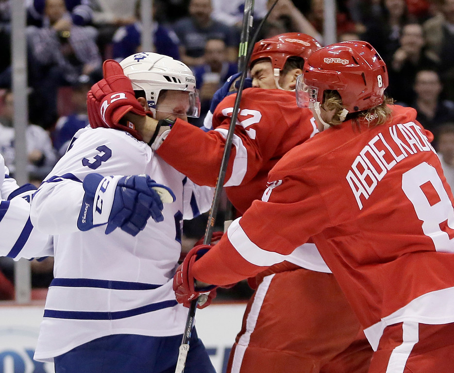 . Detroit Red Wings\' Jonathan Ericsson (52), of Sweden, gets hit in the face by Toronto Maple Leafs\' Dion Phaneuf (3) as Detroit\'s Justin Abdelkader (8) tries to break up the fight during first period of an NHL hockey games Saturday, Oct. 18, 2014, in Detroit. (AP Photo/Duane Burleson)