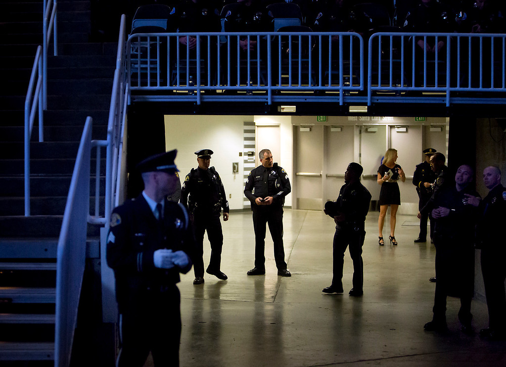 . Police officers gather at the media entrance to the HP Pavilion on Thursday morning during the memorial service for detective Sgt. Loran \'Butch\' Baker and detective Elizabeth Butler. (Kevin Johnson/Sentinel)