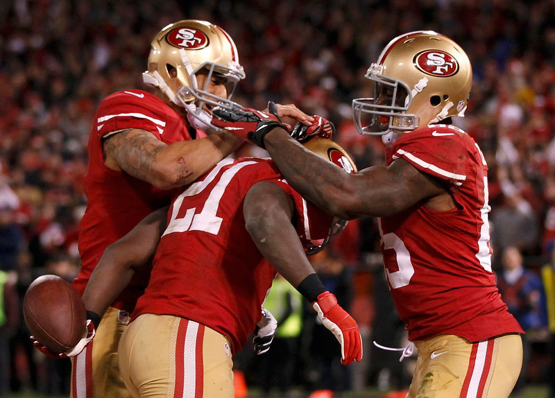 . San Francisco 49ers Frank Gore (C) is congratulated by teammates Vernon Davis (R) and Colin Kaepernick (L) after scoring a touchdown against the Green Bay Packers in the fourth quarter during their NFL NFC Divisional play-off football game in San Francisco, California January 12, 2013. REUTERS/Robert Galbraith