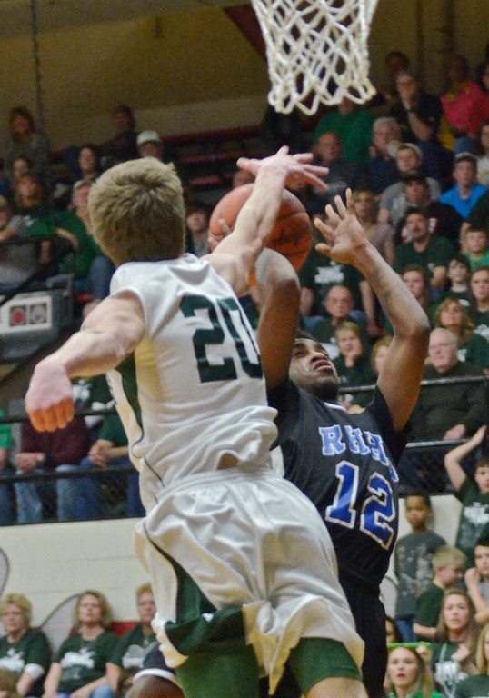 . Jeff Forman/JForman@News-Herald.com Sean Walker\'s shot is blocked by Mitch Maasz in the first half of the Spartans\' 59-45 Division IV regional semifinal win over Malvern March 11 at the Canton Field House.