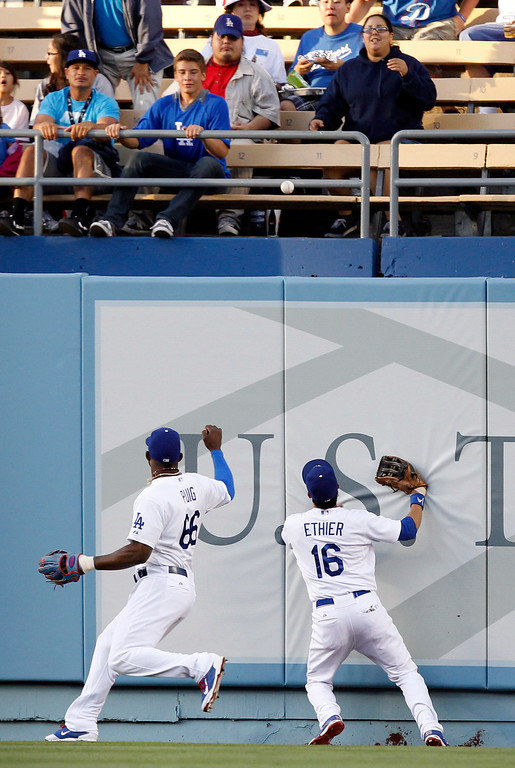 . Los Angeles Dodgers center fielder Andre Ethier (16) and right fielder Yasiel Puig (66) watch the ball bounce over the fence for a ground rule double hit by Colorado Rockies\' Justin Morneau in the first inning of a baseball game on Monday, June 16, 2014, in Los Angeles.   (AP Photo/Alex Gallardo)