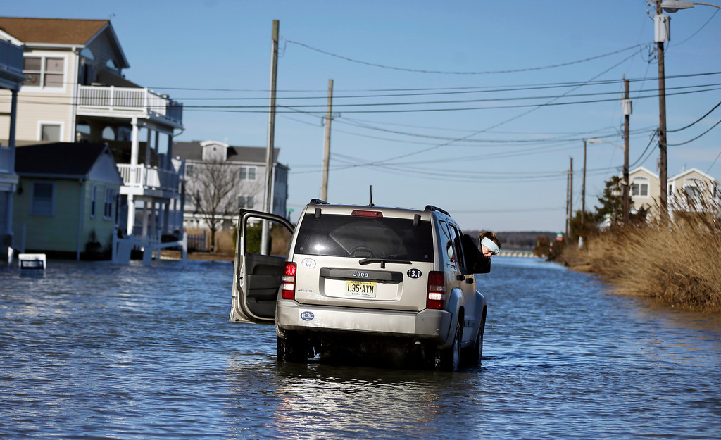 . Susie Baumgardner, of Longport, N.J., watches out a window, as she and father drive along a flooded street to check on relatives Sunday, Jan. 24, 2016, in Sea Isle City, N.J. Residents in southern New Jersey\'s coastal towns continue to deal with flooding caused by the weekend\'s major snowstorm. (AP Photo/Mel Evans)