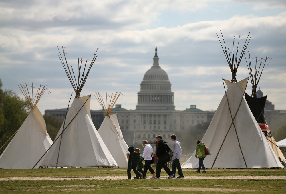 . People walk past Indian Teepees that are on the National Mall as part of a protest against the Keystone pipeline April 23, 2014 in Washington, DC. As part of its \'Reject and Protect\' protest, the Cowboy and Indian Alliance is organizing a weeklong series of actions by farmers, ranchers and tribes to show their opposition to the pipeline.  (Photo by Mark Wilson/Getty Images)