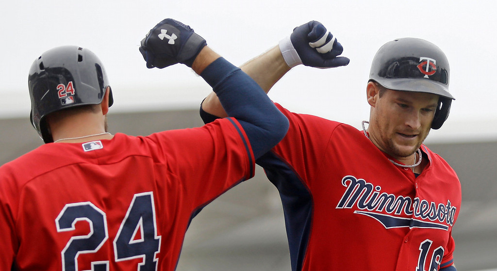 . Minnesota Twins\' Josh Willingham (16) is greeted by Trevor Plouffe (24) after hitting a solo home run during the second inning of an exhibition baseball game against the Boston Red Sox in Fort Myers, Fla., Saturday, March 29, 2014. (AP Photo/Gerald Herbert)