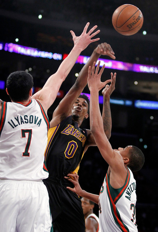 . Los Angeles Lakers forward Nick Young (0) passes the ball between Milwaukee Bucks forward Ersan Ilyasova (7) and guard Giannis Antetokounmpo during the first half of an NBA basketball game Tuesday, Dec. 31, 2013, in Los Angeles. (AP Photo/Alex Gallardo)