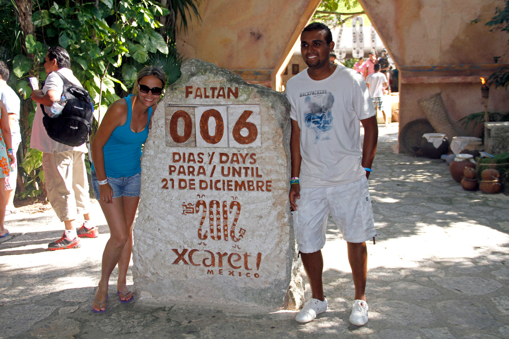 Description of . Tourists get their picture taken next to a slab of stone counting down the days until Dec. 21, 2012 at the Xcaret theme park in Playa del Carmen, Mexico, Saturday, Dec. 15, 2012. Amid a worldwide frenzy of advertisers and new-agers preparing for a Maya apocalypse, one group is approaching Dec. 21 with calm and equanimity calm: the people whose ancestors supposedly made the prediction in the first place. Mexico's 800,000 Mayas are not the sinister, secretive, apocalypse-obsessed race they've been made out to be.  (AP Photo/Israel Leal)