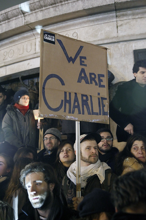 ". A man holds a placard ""We are all Charlie\"" during a gathering at the Place de la Republique (Republic square) in support of the victims after the terrorist attack earlier today on January 7, 2015 in Paris, France. Twelve people were killed including two police officers as two gunmen opened fire at the offices of the French satirical publication Charlie Hebdo.  (Photo by Thierry Chesnot/Getty Images)"