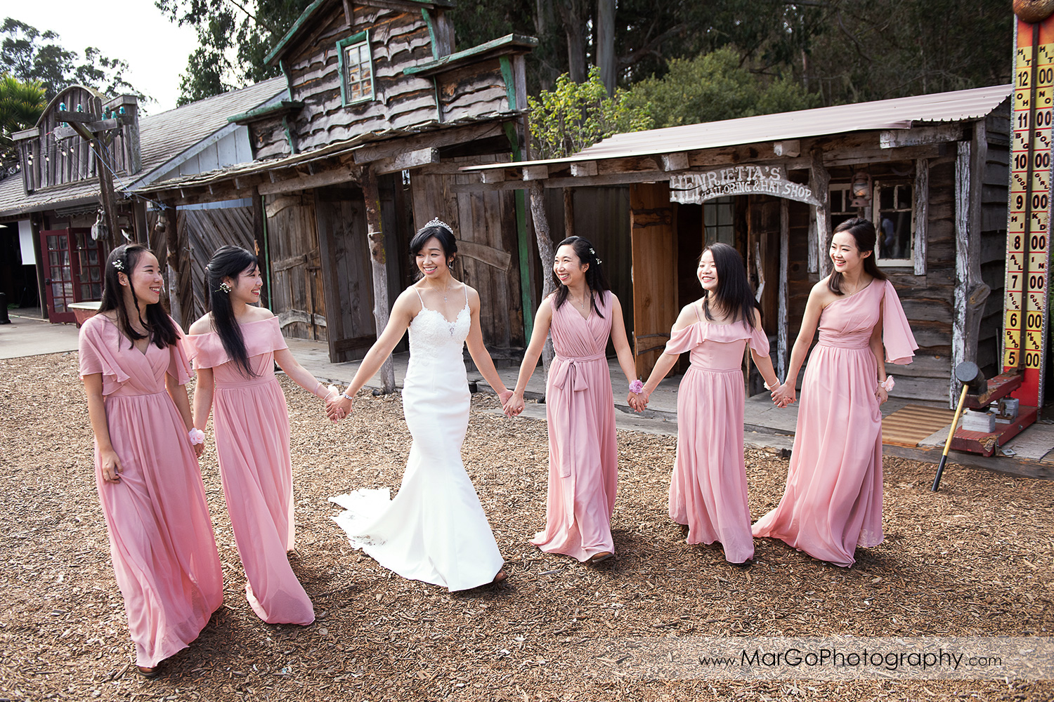 bride in white dress and bridesmaids in pink dresses walking holding hands at Long Branch Saloon & Farms in Half Moon Bay