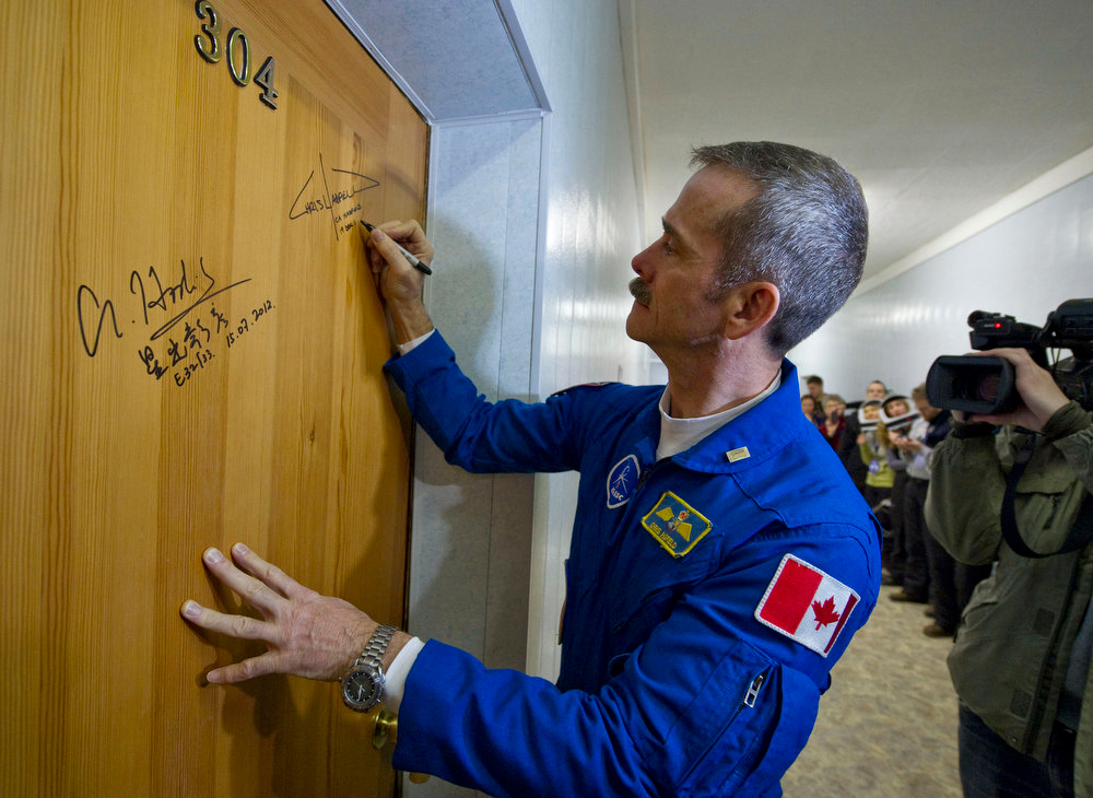 Description of . International Space Station (ISS) Canadian astronaut Chris Hadfield signs a door before leaving a hotel for a final pre-launch preparation at the Baikonur Cosmodrome, Wednesday, Dec. 19, 2012.  (AP Photo/Sergei Remezov, Pool)