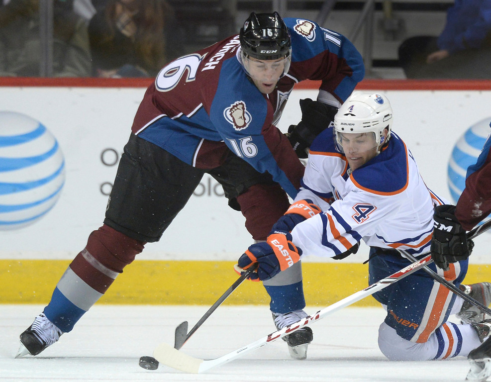 . DENVER, CO. - DECEMBER 19: Colorado defenseman Cory Sarich (16) and Edmonton wing Taylor Hall (4) fought for the puck in the third period. The Colorado Avalanche defeated the Edmonton Oilers 4-2 Thursday night, December 19, 2013.  Photo By Karl Gehring/The Denver Post