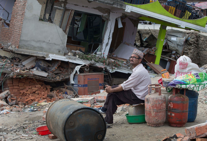 . A Nepalese man sits in front of his damaged house waiting to salvage household goods after an earthquake in Kathmandu, Nepal ,Sunday, April 26, 2015. Sleeping in the streets and shell-shocked, Nepalese cremated the dead and dug through rubble for the missing Sunday, a day after a massive Himalayan earthquake devastated the region and destroyed homes and infrastructure. (AP Photo/Manish Swarup)