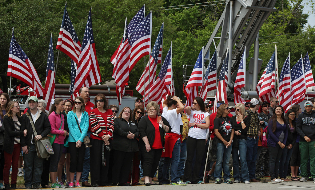 . People stand in front of American flags as fire departments from around Texas pay their respects during a parade for the West Memorial Service on April 25, 2013 in Waco, Texas.  (Photo by Erich Schlegel/Getty Images)