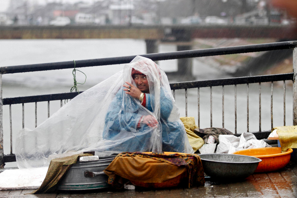 . A Kashmiri fish vendor wraps herself with a plastic sheet to protect herself from the rain as she sits awaiting customers in Srinagar, India, Tuesday, Feb. 5, 2013. (AP Photo/Mukhtar Khan)