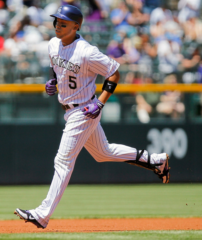 . Colorado Rockies\' Carlos Gonzalez rounds the bases after hitting a home run off Arizona Diamondbacks\' Trevor Cahill during the first inning of a baseball game on Wednesday, May 22, 2013, in Denver. (AP Photo/Barry Gutierrez)