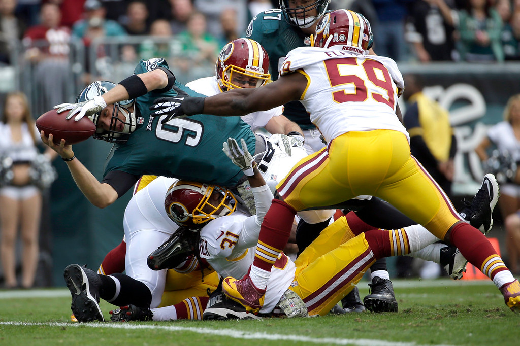 . Philadelphia Eagles quarterback Nick Foles (9) dives into the end zone for a touchdown as Washington Redskins inside linebacker London Fletcher (59) reaches to stop him during the first half of an NFL football game in Philadelphia, Sunday, Nov. 17, 2013. (AP Photo/Matt Slocum)