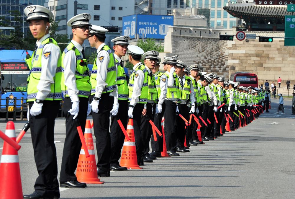 ". Policemen stand guard as South Korean workers march during a May Day rally in Seoul on May 1, 2014. The rally drew around 5,000 people who denounced President Park Geun-Hye and urged her to take responsibility for the government\'s ""bungled and incompetent\"" response to the  ferry disaster that claimed the lives of hundreds of schoolchildren.  (JUNG YEON-JE/AFP/Getty Images)"