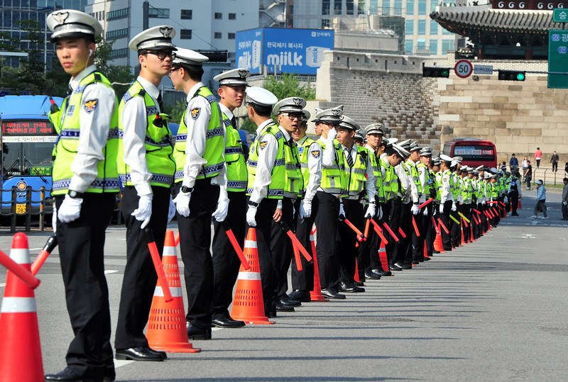 """. Policemen stand guard as South Korean workers march during a May Day rally in Seoul on May 1, 2014. The rally drew around 5,000 people who denounced President Park Geun-Hye and urged her to take responsibility for the government\'s \""""bungled and incompetent\"""" response to the  ferry disaster that claimed the lives of hundreds of schoolchildren.  (JUNG YEON-JE/AFP/Getty Images)"""