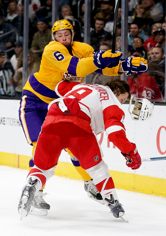 . Los Angeles Kings defenseman Jake Muzzin (6) checks Detroit Red Wings left wing Justin Abdelkader during the first period of an NHL hockey game in Los Angeles, Tuesday, Feb. 24, 2015. (AP Photo/Chris Carlson)