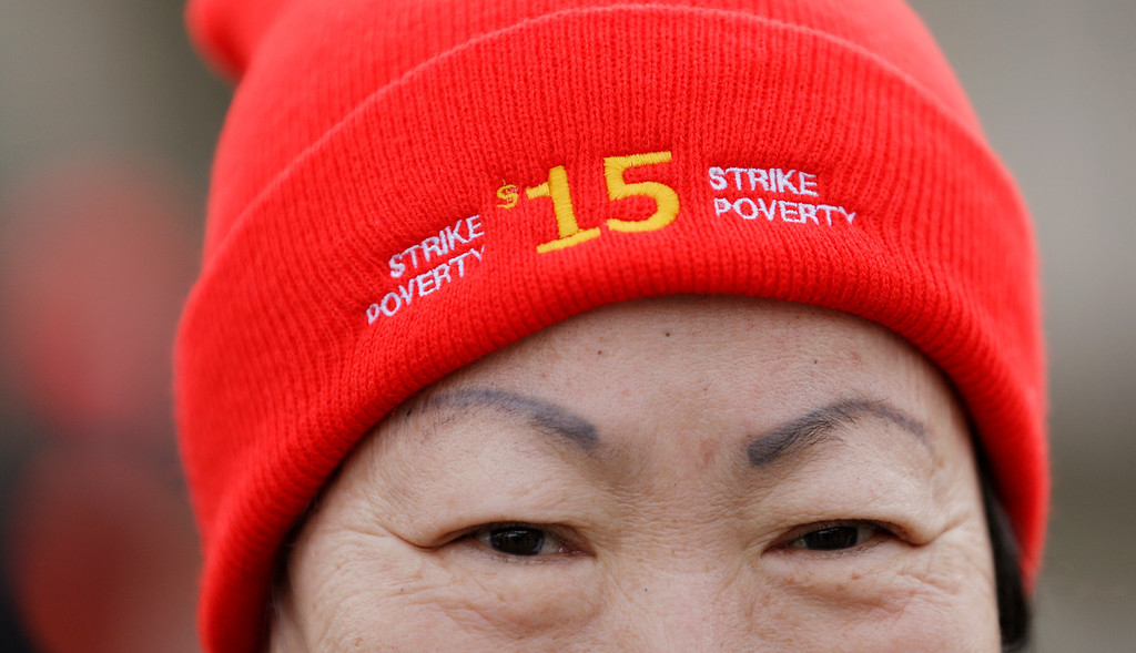 . Sun Benjamin, a home health care worker, looks out from under a cap advocating a $15 minimum wage as she prepares to walk with other protesters on a day-long march in support of fast-food workers Thursday, Dec. 5, 2013, in SeaTac, Wash.  (AP Photo/Elaine Thompson)