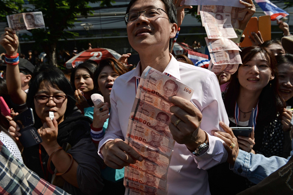 . Supporters hold bank notes to donate to Thai protest leader Suthep Thaugsuban (not pictured) as anti-government protesters march in downtown Bangkok as part of their ongoing rallies on January 21, 2014.  Demonstrators have been staging \'shutdown\' protests for more than a week in the Thai capital in their bid to force Prime Minister Yingluck Shinawatra from power and topple her government. (CHRISTOPHE ARCHAMBAULT/AFP/Getty Images)