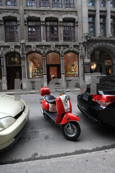 A rider finds just enough room to park his scooter between two cars in downtown Montreal, Quebec.