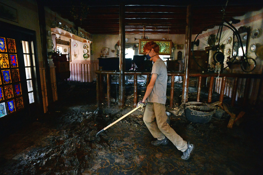 . GLEN HAVEN, CO - OCTOBER 8: Volunteer Caleb Johnson pushes a shovelful of mud  up off the carpet to throw out of the window at the historic Glen Haven Inn in Glen Haven, CO on October 8, 2013.  The Inn was one of the only businesses that actually made it in the town but has been inundated with mud and debris.  The water line along the walls suggest that the flood waters reached at least four feet inside the building.  (Photo By Helen H. Richardson/ The Denver Post)