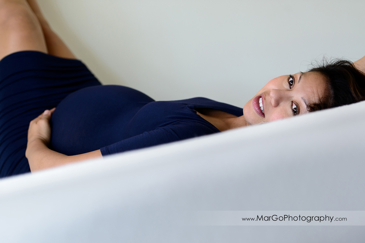 portrait of pregnant woman in navy blue dress laying on white bed