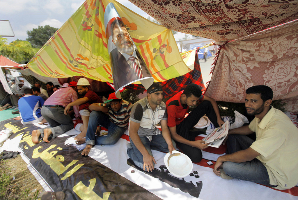 . Egyptian supporters of Egypt\'s Islamist President Mohammed Morsi read newspapers under his poster at their camp outside of the Rabia el-Adawiya mosque near the presidential palace, in Cairo, Egypt, Tuesday, July 2, 2013. (Associated Press: Amr Nabil)