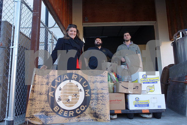 12/7/17 Contributed photo by David Huck Mayor Erin Stewart stands with Alvarium co-owner Chris DeGasero in front of over 500 pounds of food being donated through efforts by Alvarium to the HRA food pantry.