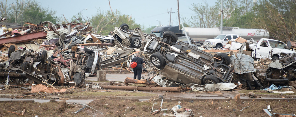 . A rescue worker looks for victims in the Moore Hospital parking lot after being hit by a F-5 tornado that destroyed buildings and overturned cars are seen after a huge tornado struck Moore, Oklahoma, near Oklahoma City, May 20, 2013.  A huge tornado with winds of up to 200 miles per hour (320 kph) devastated the Oklahoma City suburb of Moore on Monday, ripping up at least two elementary schools and a hospital and leaving a wake of tangled wreckage. 