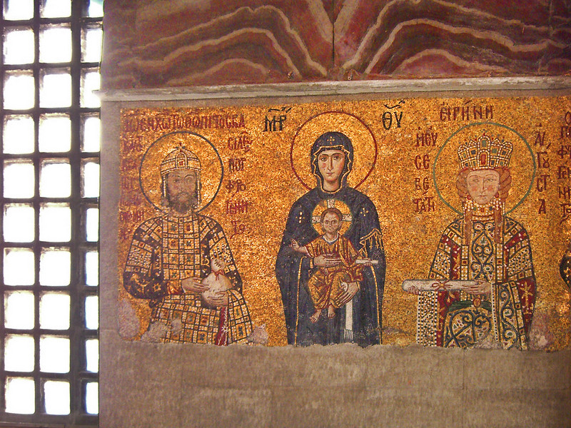 80. Comnenus mosaic, 1122. Virgin Mary in center in a dark blue gown, the Child Christ on her lap. He gives his blessing with his right hand while holding a scroll in his left hand. On the left, emperor John II Comnenus holds a purse, symbol of an imperial donation to the church. Empress Irene is on the right, offering a document.