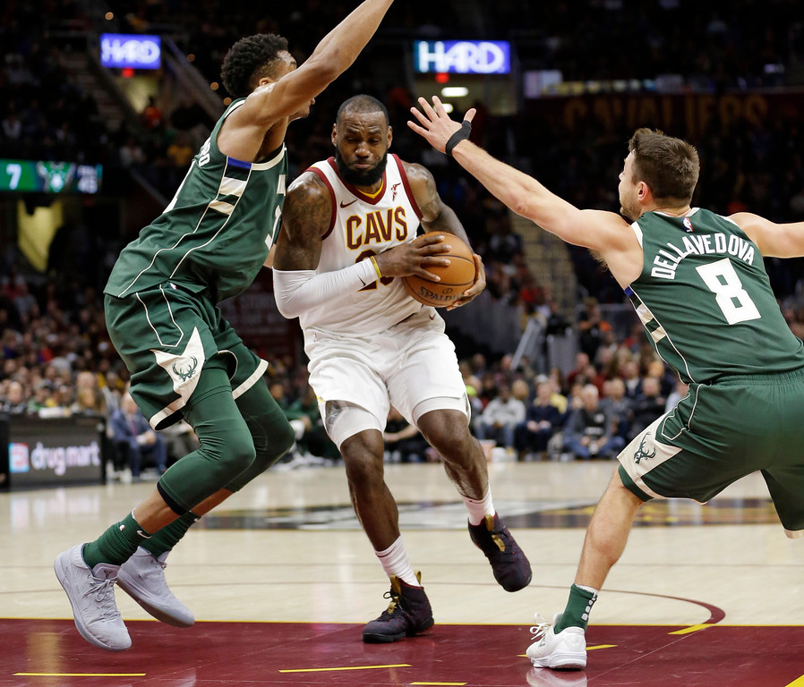 . Cleveland Cavaliers\' LeBron James, center, drives between Milwaukee Bucks\' Giannis Antetokounmpo, left, from Greece, and Matthew Dellavedova, from Australia, in the first half of an NBA basketball game, Tuesday, Nov. 7, 2017, in Cleveland. (AP Photo/Tony Dejak)