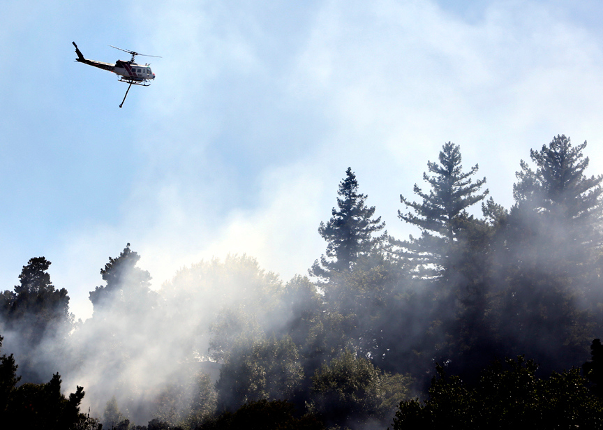 . A helicopter soars over a patch of smoldering brush as smoke bellows from a wildfire that ignited near southbound Highway 17 at the Fishhook in Santa Cruz on Thursday, June 20. (Kevin Johnson/Sentinel)