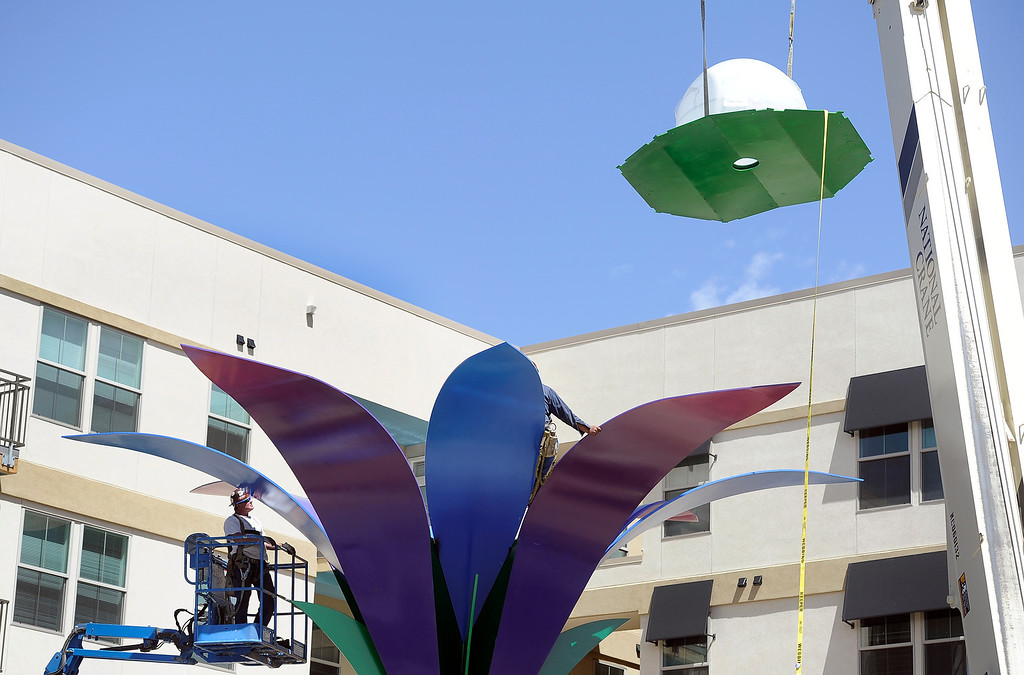 . Iron workers Brad Weaver, right, and Rex Stacy from Peak Custom Fabrication, prepare a 30 foot-tall, 10-ton metal sculpture of a large flower titled Flor De La Alma by Denver artist Emanuel Martinez, so it can be topped off with a large white bulb that serves as the center of the flower, June 25, 2013.  (Photo By Kathryn Scott Osler/The Denver Post)