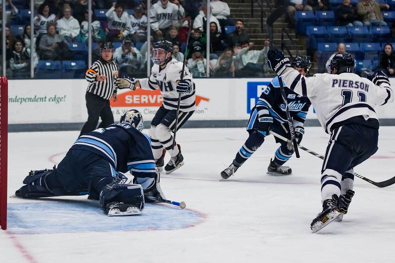 New Hampshire's Ara Nazarian (22) celebrates after scoring on a pass from teammate Jackson Pierson (11) during Hockey East action against Maine in Durham Friday. [Scott Patterson/Fosters.com]