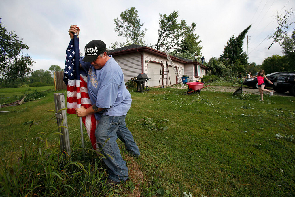 . Betsy Sadenwassen places her flag after her Hortonville, Wis., house sustained damage from Tuesday night\'s storms. (AP Photo/The Post-Crescent, Sharon Cekada)