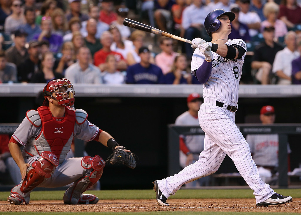 . DENVER, CO - AUGUST 14:  Corey Dickerson #6 of the Colorado Rockies hits a sacrifice fly off of starting pitcher Alfredo Simon #31 of the Cincinnati Reds to score Charlie Blackmon #19 of the Colorado Rockies and tie the score 2-2 as catcher Devin Mesoraco #39 of the Cincinnati Reds looks on in the third inning at Coors Field on August 14, 2014 in Denver, Colorado.  (Photo by Doug Pensinger/Getty Images)