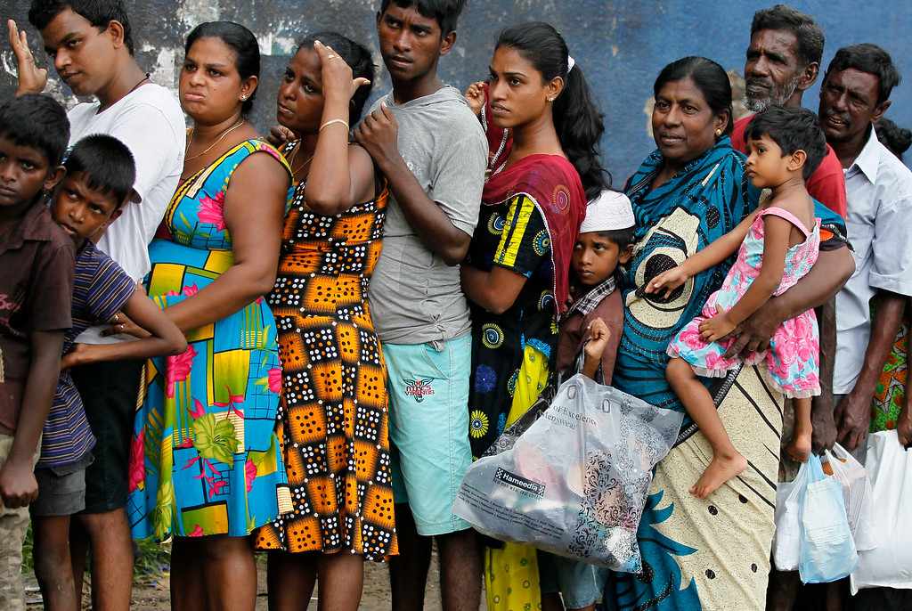 . Sri Lankan flood victims line up to receive relief materials in a flood affected area near Colombo, Sri Lanka, Sunday, May 22, 2016. Sri Lanka\'s soldiers continued searching for scores of people missing since deadly landslides struck hill country several days ago leaving dozens dead. (AP Photo/Eranga Jayawardena)