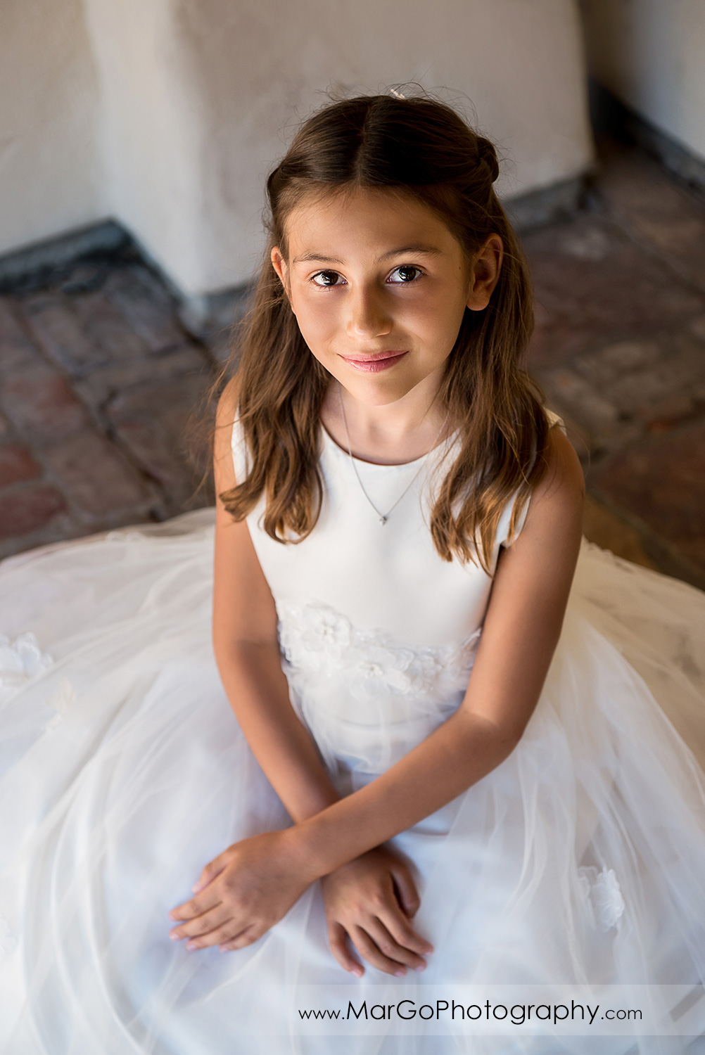 first communion girl in white dress sitting on the bench at Cafe Wisteria in Menlo Park