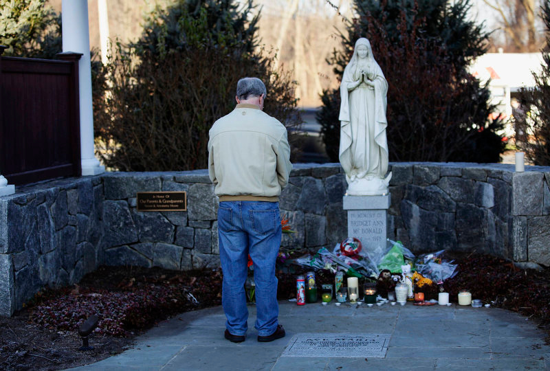 . A man bows his head as he stands at a makeshift memorial, outside Saint Rose of Lima Roman Catholic Church in Newtown, Connecticut December 15, 2012. People in the small Connecticut community of Newtown grieved on Saturday over one of the worst mass shootings in U.S. history and police sought answers about what drove a 20-year-old gunman to slaughter 20 children at Sandy Hook Elementary School.  REUTERS/Joshua Lott