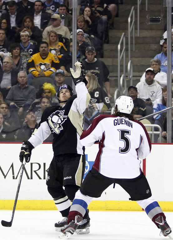 . Sidney Crosby #87 of the Pittsburgh Penguins reaches for a puck against Nate Guenin #5 of the Colorado Avalanche during the game at Consol Energy Center on October 21, 2013 in Pittsburgh, Pennsylvania.  (Photo by Justin K. Aller/Getty Images)