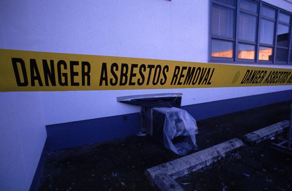 Danger Asbestos Removal warning ribbon around building.