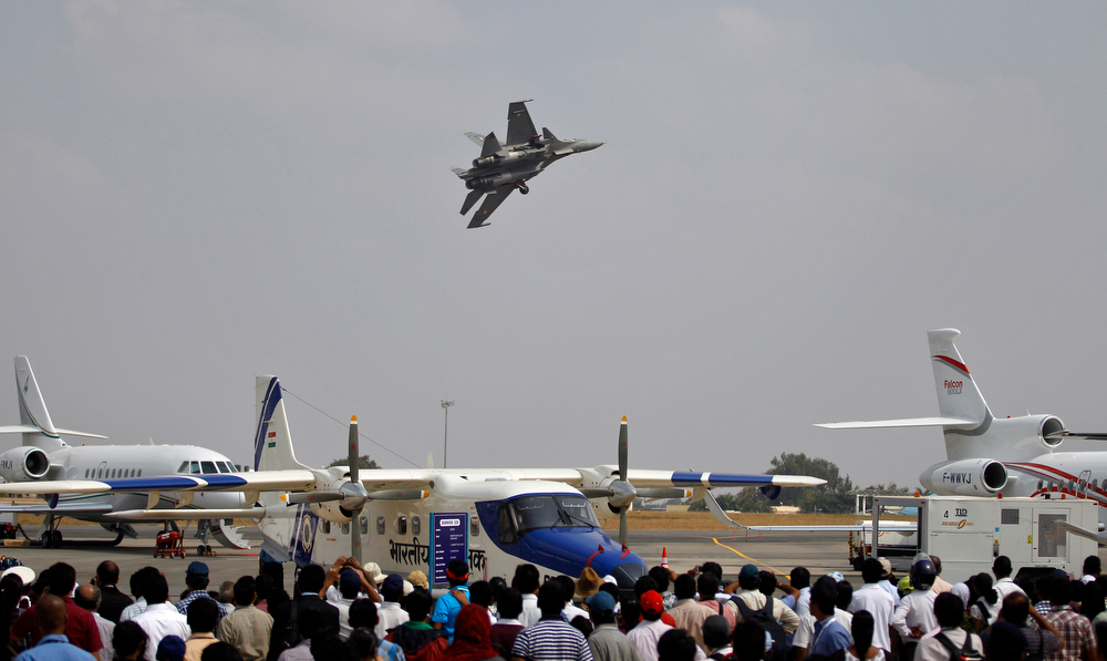 Description of . Visitors watch a Sukhoi Su-30 fighter aircraft fly over other aircraft on display on the third day of the Aero India 2013 at Yelahanka air base in Bangalore, India, Friday, Feb. 8, 2013. More than 600 aviation companies along with delegations from 78 countries are participating in the five-day event that started Wednesday. (AP Photo/Aijaz Rahi)