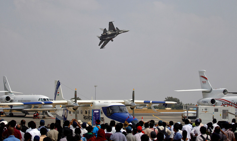 . Visitors watch a Sukhoi Su-30 fighter aircraft fly over other aircraft on display on the third day of the Aero India 2013 at Yelahanka air base in Bangalore, India, Friday, Feb. 8, 2013. More than 600 aviation companies along with delegations from 78 countries are participating in the five-day event that started Wednesday. (AP Photo/Aijaz Rahi)