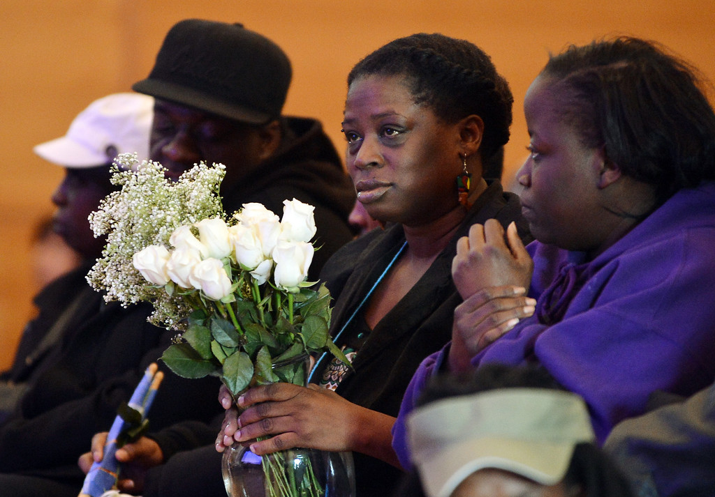 . Dinyal New, center, mother of slain teenager Lee Weathersby III, holds a bouquet of flowers during a memorial service for her son held at Alliance Academy in Oakland, Calif. on Wednesday, Jan. 8, 2014. (Kristopher Skinner/Bay Area News Group)