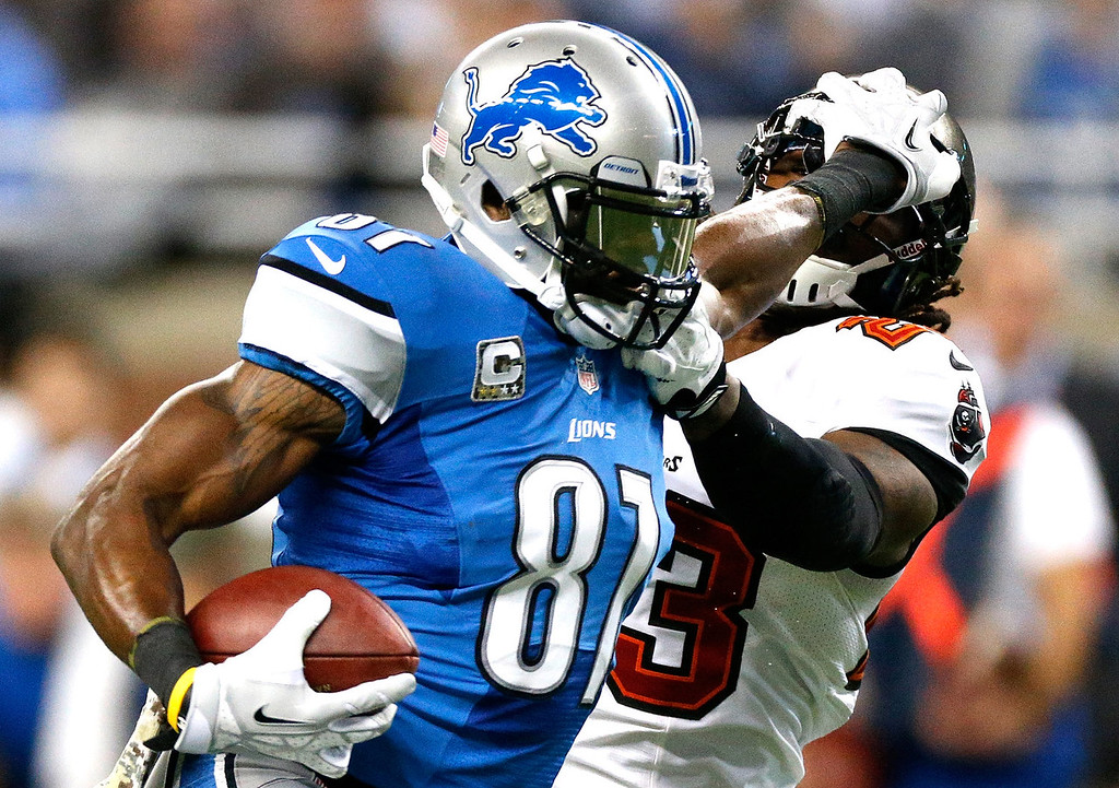 . Calvin Johnson #81 of the Detroit Lions stiff arms Mark Barron #23 of the Tampa Bay Buccaneers in the second quarter at Ford Field on November 24, 2013 in Detroit, Michigan. (Photo by Gregory Shamus/Getty Images)