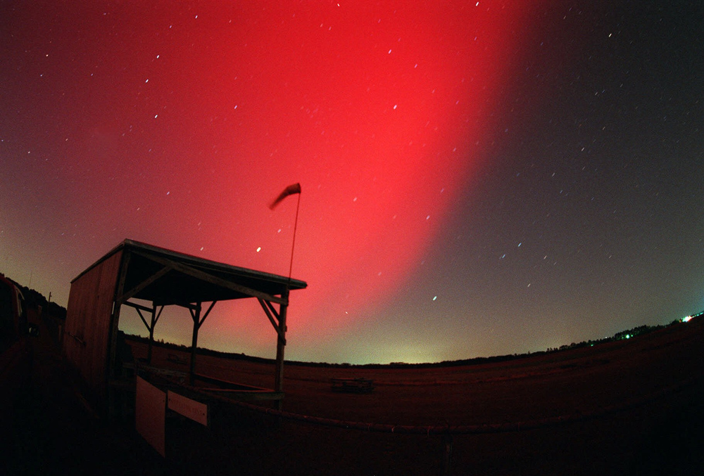 . The red glow of the aurora borealis covers the northeastern sky around 9:30 pm, EDT, Thursday, April 6,, 2000 in this fish-eye view taken 10 miles northeast of Fayetteville, N.C. Solar flares cause the aurora or \'northern lights.\'  A shed and windsock used by a local model aircraft flying club sits in the foreground.  (AP Photo, The Fayetteville Observer, Johnny Horne)