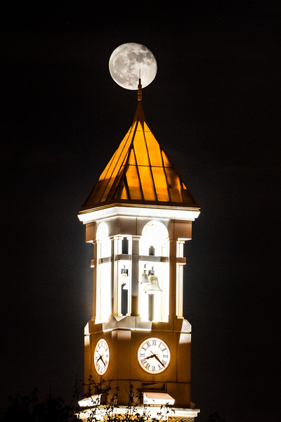 A full moon positioned behind the Bell Tower at Purdue University with the spire at the top pointing to Neil Armstrong's Apollo 11 landing site.