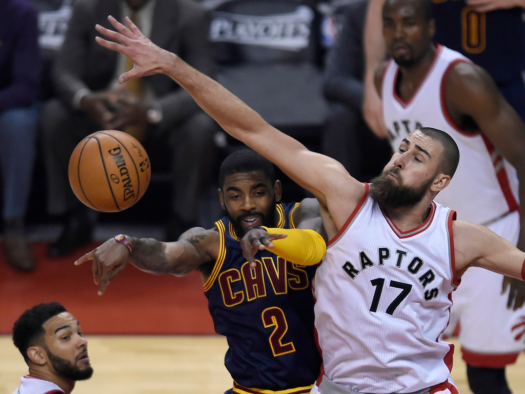 . Cleveland Cavaliers guard Kyrie Irving passes the ball past Toronto Raptors center Jonas Valanciunas during the first half of Game 4 of the second round of the NBA playoffs in Toronto on May 7. The Cavaliers won, 109-102, to sweep the series. Irving led the Cavs in assists (9), while LeBron James led in points (35) and rebounds (9). (Nathan Denette/The Canadian Press via AP) Press via AP)